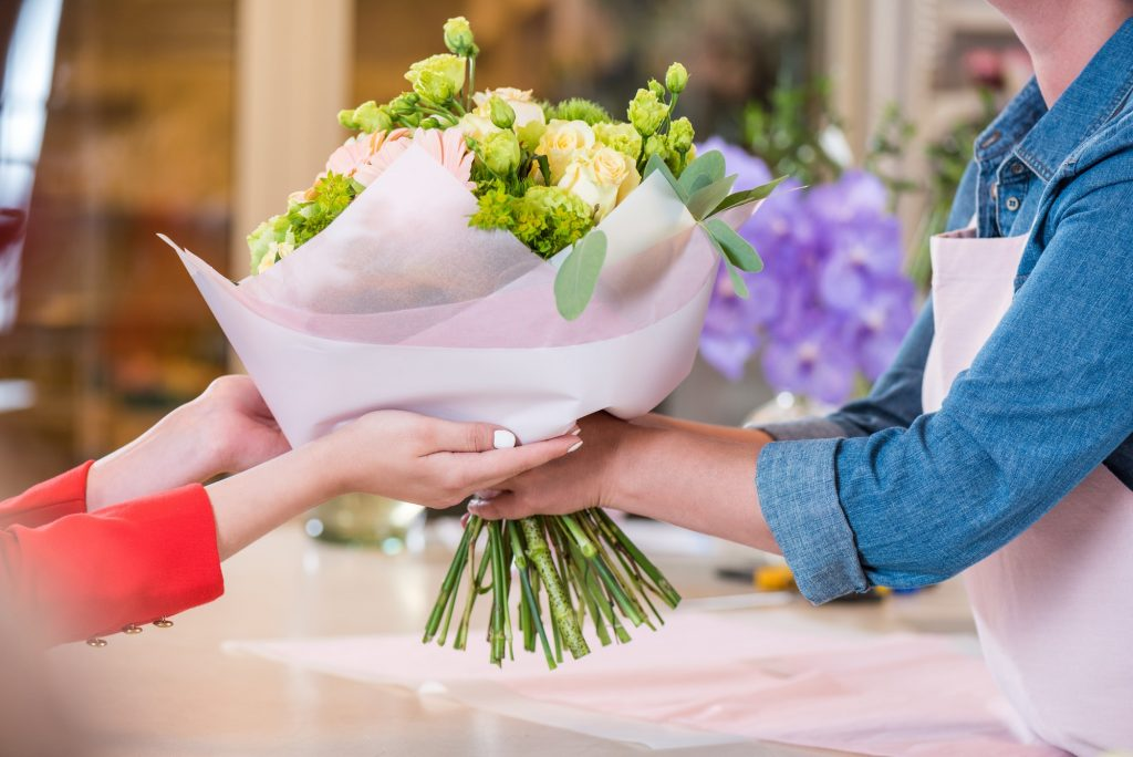 cropped shot of florist giving beautiful flower bouquet to client